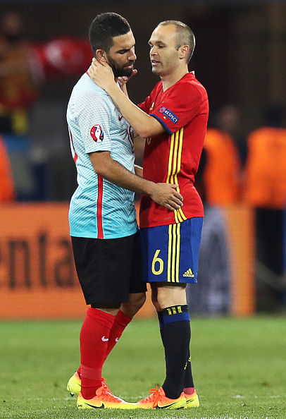 Spain's midfielder Andres Iniesta (R) encourages Turkey's midfielder Arda Turan following the Euro 2016 group D football match between Spain and Turkey at the Allianz Riviera stadium in Nice on June 17, 2016. / AFP / Valery HACHE (Photo credit should read VALERY HACHE/AFP/Getty Images)