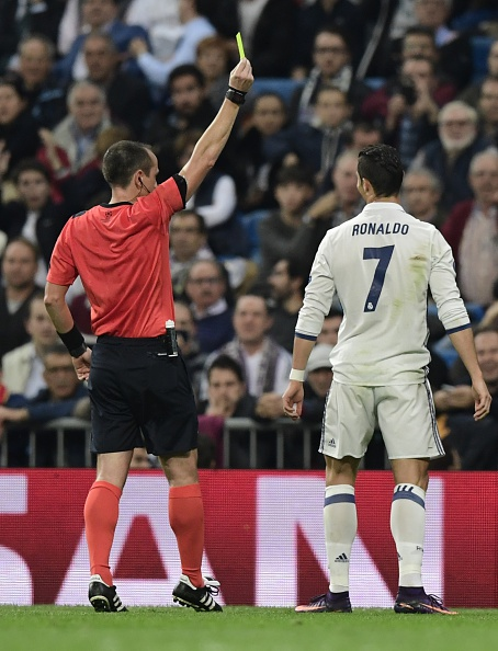 The referee (L) shows a yellow card to Real Madrid's Portuguese forward Cristiano Ronaldo during the UEFA Champions League football match Real Madrid CF vs Legia Legia Warszawa at the Santiago Bernabeu stadium in Madrid on October 18, 2016. / AFP / JAVIER SORIANO (Photo credit should read JAVIER SORIANO/AFP/Getty Images)
