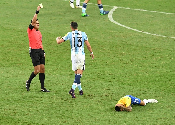 Chilean referee Julio Bascunan yellow cards Argentina's Ramiro Funes Mori for a foul over Brazil's Neymar during the 2018 FIFA World Cup qualifier football match Brazil vs Argentina, in Belo Horizonte, Brazil, on November 10, 2016. / AFP / EVARISTO SA        (Photo credit should read EVARISTO SA/AFP/Getty Images)