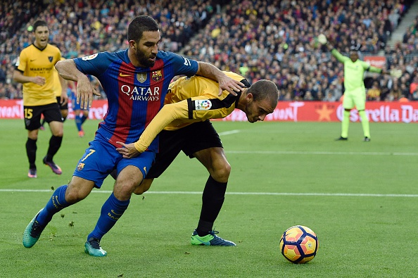 Barcelona's Turkish forward Arda Turan (L) vies with Malaga's Venezuelan defender Mikel Villanueva (R) during the Spanish league football match between FC Barcelona and Malaga CF at the Camp Nou stadium in Barcelona, on November 19, 2016. / AFP / LLUIS GENE        (Photo credit should read LLUIS GENE/AFP/Getty Images)